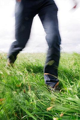 Legs of man running across field - p597m1465132 by Tim Robinson