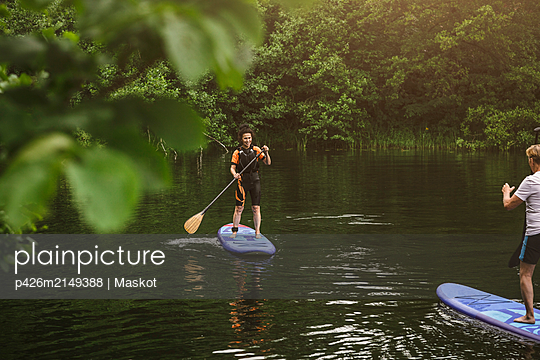 Senior woman and man learning paddleboarding in sea during SUP course - p426m2149388 by Maskot