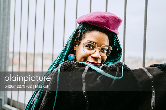 Portrait of smiling mid adult woman with blue braided hair wearing beret by fence - p426m2279762 by Maskot