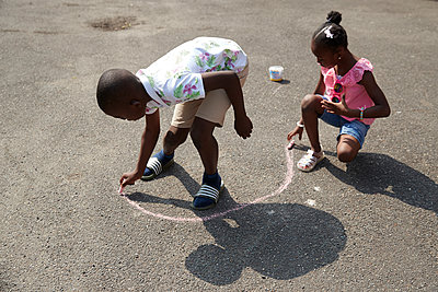 Brother and sister playing with sidewalk chalk on sunny pavement - p1023m2238479 by Himalayan Pics