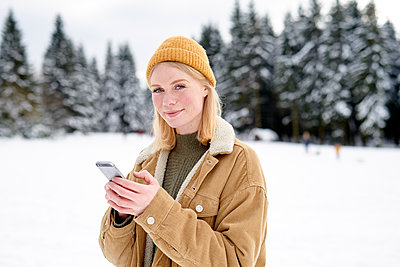 Woman using smartphone in snow-capped landscape - p1124m1589299 by Willing-Holtz