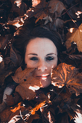 Young woman's face with leaves around the head - p1628m2233791 by Lorraine Fitch
