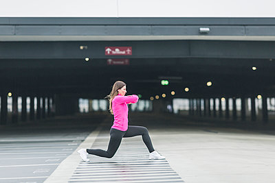 Woman stretching at parking garage - p300m1204668 by Anke Scheibe