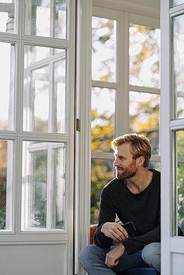 Man sitting in sunroom at home - p300m2167226 by Kniel Synnatzschke