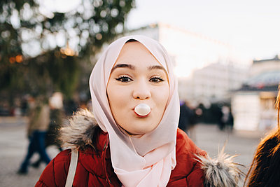 Portrait of young Muslim woman blowing bubble gum in city - p426m1556072 by Maskot