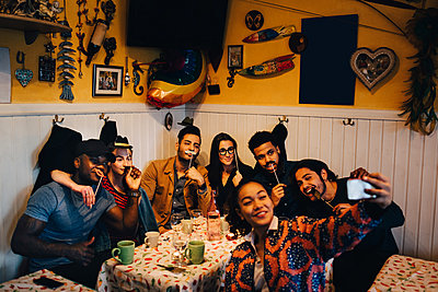 Young woman taking selfie with cheerful multi-ethnic friends holding props while sitting at restaurant during dinner par - p426m2046275 by Maskot