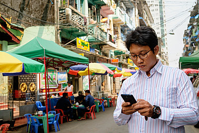 Asian businessman using cell phone in city - p555m1410872 by Roberto Westbrook