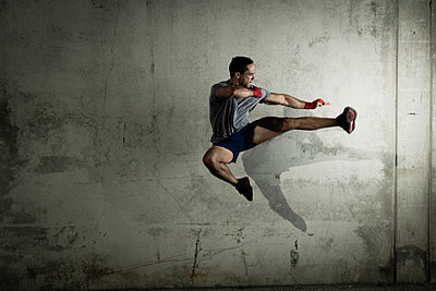Kickboxer, in urban environment, mid air, in jump - p924m1230268 by Wil Cohen