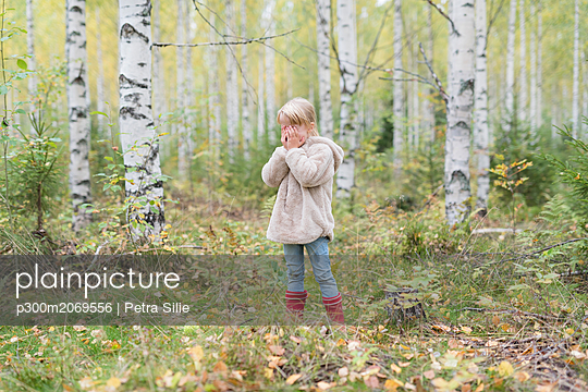 Blond girl playing Hide and Seek in a birch forest - p300m2069556 by Petra Silie