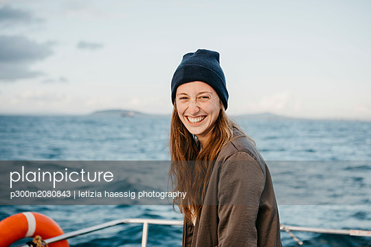 South Africa, young woman with woolly hat smiling during boat trip at sunset - p300m2080843 by letizia haessig photography
