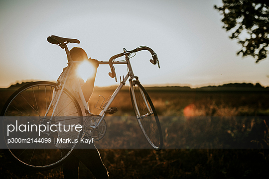 Man carrying a racing cycle in the sunshine - p300m2144099 by Markus Kayl