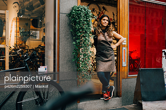 Businesswoman with hand on hip standing on doorway of bicycle shop - p426m2259307 by Maskot