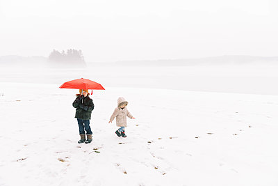 A brother and sister having fun in the wintery rain. - p1166m2157464 by Cavan Images