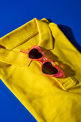 A folded yellow polo shirt and a pair of heart-shaped sunglasses on a blue background - p1423m2212031 by JUAN MOYANO