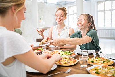 Young woman is sharing pizza - p276m2110740 by plainpicture