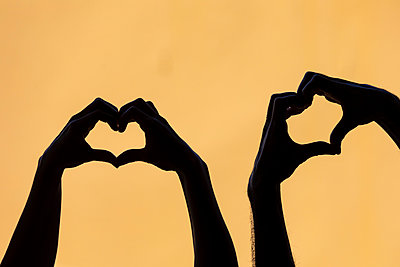 Couple mankink heart shape finger frames against yellow background - p300m2199619 by William Perugini