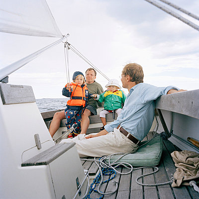 Two men and two children on a sailing boat Sweden - p31222812 by Lena Granefelt