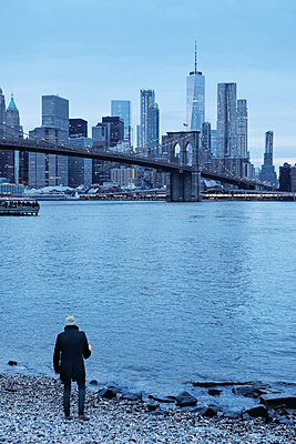 Man looking out over Brooklyn Bridge and Lower Manhattan Skyline from riverbank, New York, USA - p924m1568844 by Seth K. Hughes