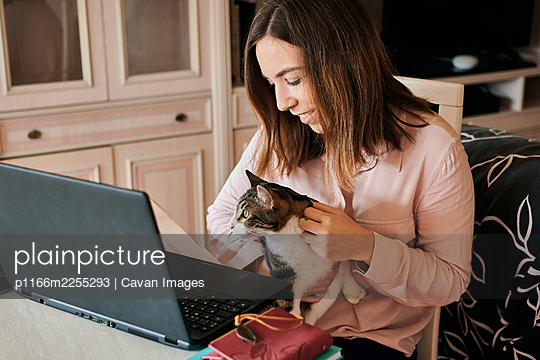 Young woman pets her cat while she is working from home - p1166m2255293 by Cavan Images