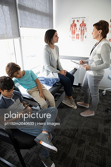 Female doctor talking to mother with sons in clinic examination room - p1192m2040633 by Hero Images