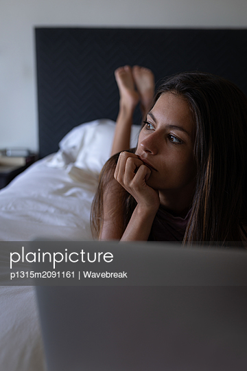 Woman lying at bed while using laptop on bed at home - p1315m2091161 by Wavebreak