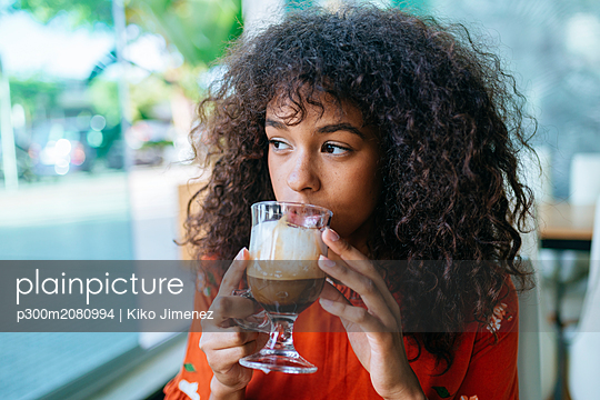 Portrait of young woman drinking coffee in a cafe while looking out of window - p300m2080994 by Kiko Jimenez