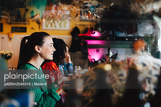 Smiling young woman gesturing while sitting with multi-ethnic friends at restaurant during brunch - p426m2046316 by Maskot