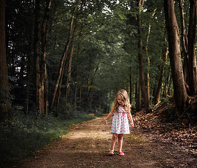 Girl standing on dirt road amidst forest - p1166m1509129 by Cavan Images