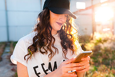 Cheerful millennial woman using smartphone in street at sunset - p1166m2148851 by Cavan Images