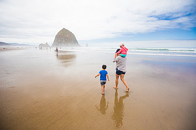Mother and two kids walk toward Haystack Rock, Cannon Beach. - p1166m2157209 by Cavan Images