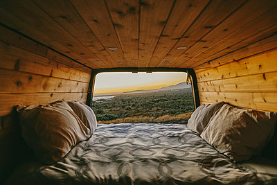 Sunset view of ocean over cliffs from bed of sprinter van in Mexico. - p1166m2202029 by Cavan Images