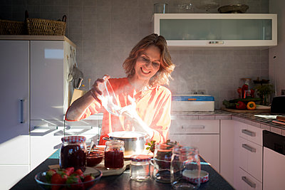 Smiling woman making strawberry jam in kitchen at home - p300m1568300 by Robijn Page