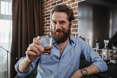 Portrait of smiling man with glass of whiskey at home - p300m1568556 by Vasily Pindyurin
