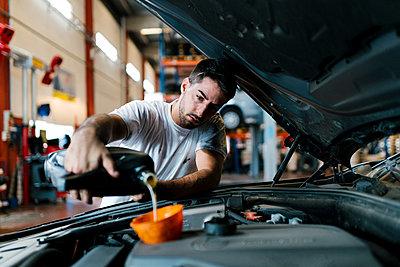 Auto mechanic filling engine oil while standing in garage - p300m2220933 by Ezequiel Giménez