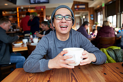 Laughing Asian man in coffee shop - p555m1304005 by Granger Wootz