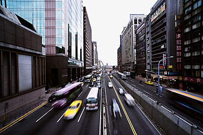 Tall buildings frame an arterial avenue along which traffic rushes, Taipei, Taiwan, Asia - p934m832683 by Raphaël Olivier
