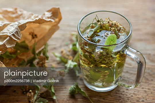 Fresh lime tea by dried linden leaves in paper bag on wooden cutting board - p300m2256738 by Vladimir Godnik