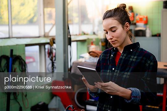 Female mechanic using digital tablet at repair shop - p300m2290588 by Kniel Synnatzschke