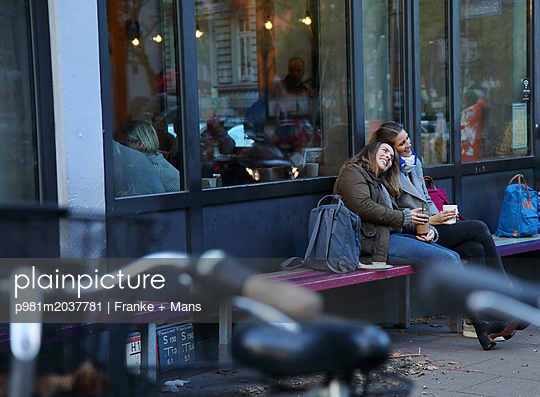 Freundinnen vorm Café - p981m2037781 von Franke + Mans