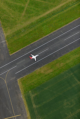 Aerial view of airport runway with private jet - p1048m2088104 by Mark Wagner