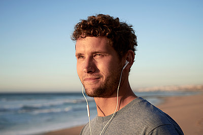 Man with earphones on beach - p1124m1510937 by Willing-Holtz