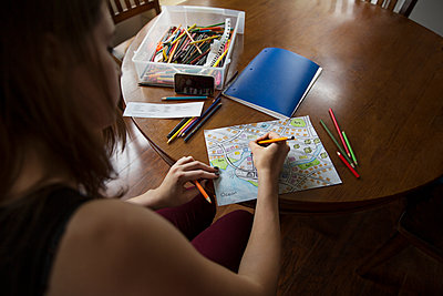 Teenage girl (14-15) drawing map sitting at table - p1166m1086025f by Geoff Hannert