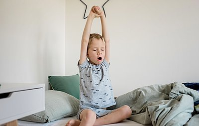 young boy waking up from a sleep and yawning in his bedroom - p1166m2147372 by Cavan Images