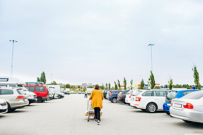 Rear view of young woman pushing shopping cart in car park - p1264m1089031f by Astrakan