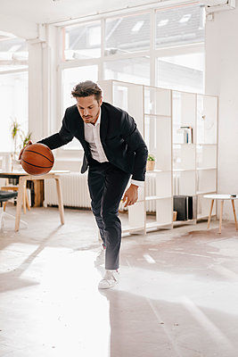Businessman playing basketball in office - p300m1459771 by Kniel Synnatzschke