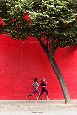 Two sporty young women running together in the city passing red wall - p300m2083540 by Josep Suria
