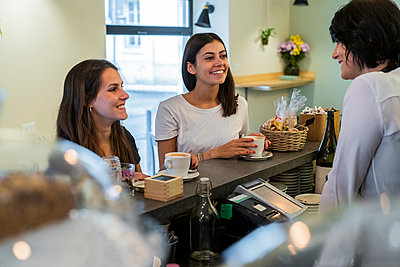 Two happy young female friends at the counter in a cafe - p300m2139902 by Giorgio Fochesato
