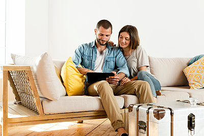 Smiling couple at home in modern living room sitting on couch while looking at tablet together - p300m2181122 by Steve Brookland