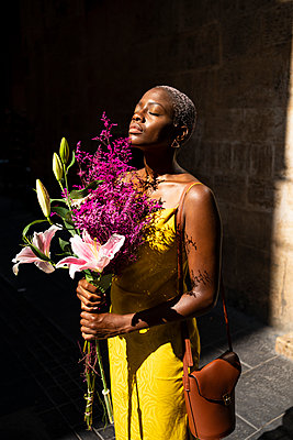 Mid adult woman with eyes closed holding flower bouquet on sunny day - p300m2241651 by Rafa Cortés