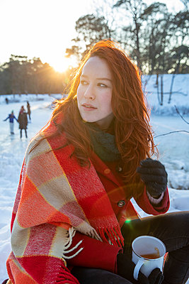Redhead woman wrapped in blanket holding coffee mug while looking away during sunset - p300m2287412 by Frank van Delft